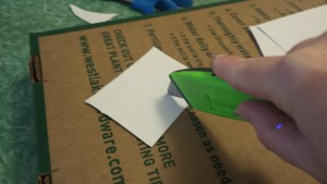 Cutting stencils from thin cardboard.